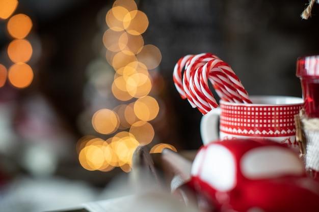 Des tasses de noël rouges avec des bonbons sont sur la table sur le fond de l'arbre de noël