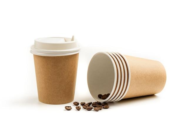 Tasses en papier à emporter et grains de café isolés sur fond blanc.