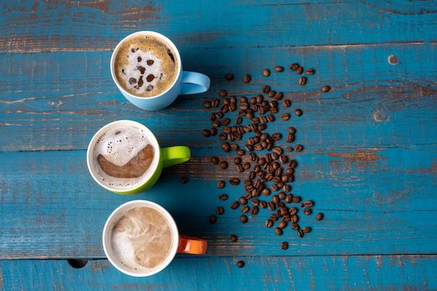 Tasses à plat avec du café sur fond en bois bleu, copiez l'espace pour le texte.