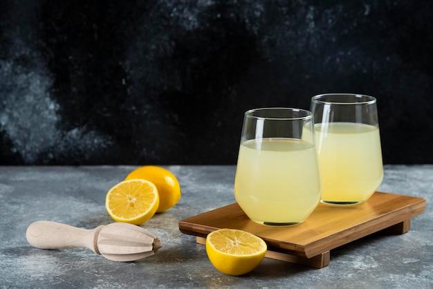 Tasses pleines de limonade avec des tranches de citron et un alésoir en bois.