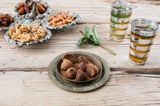 Tasses près de rameau de plante, bonbons au chocolat, fruits secs et noix à bord