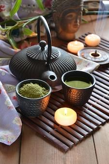 Tasses remplies de thé japonais, d'eau chaude, d'encens et de bougies
