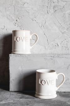 Tasses roses avec amour, fond gris. concept de rencontre romantique, amour, petit déjeuner romantique