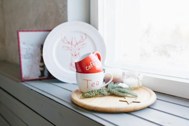 Tasses rouges et blanches pour le thé et le café sur un rebord de fenêtre dans un décor d'intérieur