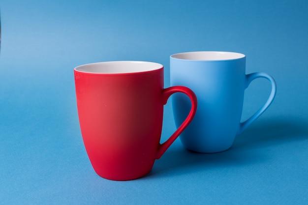 Tasses rouges et bleues sur fond bleu.