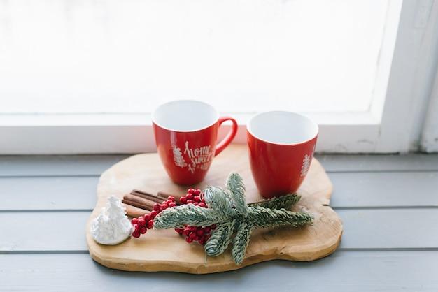Tasses rouges avec du thé, du café ou du vin chaud sur le rebord de la fenêtre dans le décor d'une maison