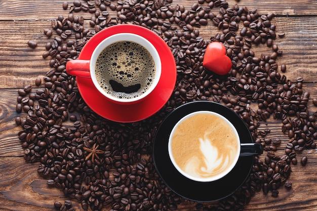 Tasses rouges et noires de café, de grains et de coeur sur une table en bois