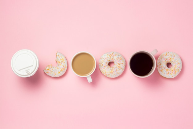 Tasses et tasse de papier avec du café ou du thé, des beignets sucrés savoureux frais exposés en ligne sur un fond rose. concept de restauration rapide, boulangerie, petit déjeuner, bonbons, café. mise à plat, vue de dessus, espace copie.