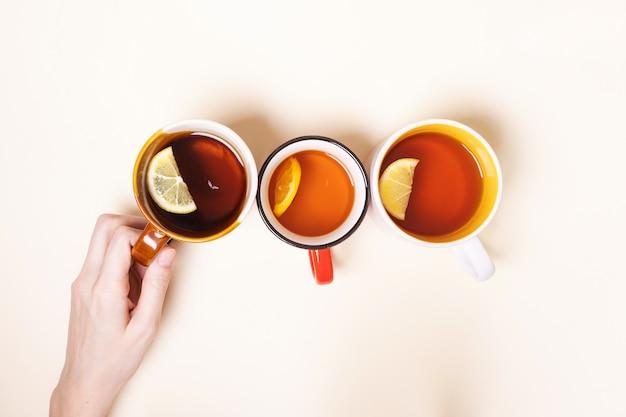 Tasses à thé au citron sur fond beige.