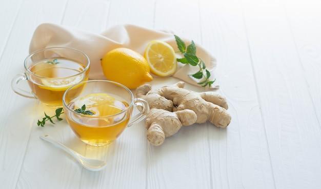 Tasses de thé au gingembre sain avec des feuilles de menthe et de citron sur une table en bois blanc