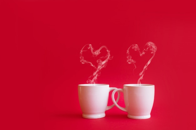 Tasses de thé ou de café à la vapeur en forme de deux coeur sur fond rouge. concept de célébration ou d'amour de la saint-valentin. espace copie