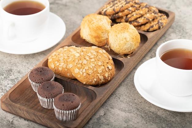 Tasses de thé chaud avec assiette de divers bonbons sur la table.