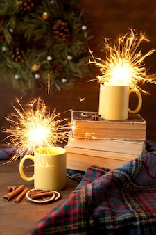 Tasses à thé jaunes avec fond scintillant et noël, tasse en céramique avec lumière vive à l'intérieur, livres et couverture avec rouleaux et cannelle