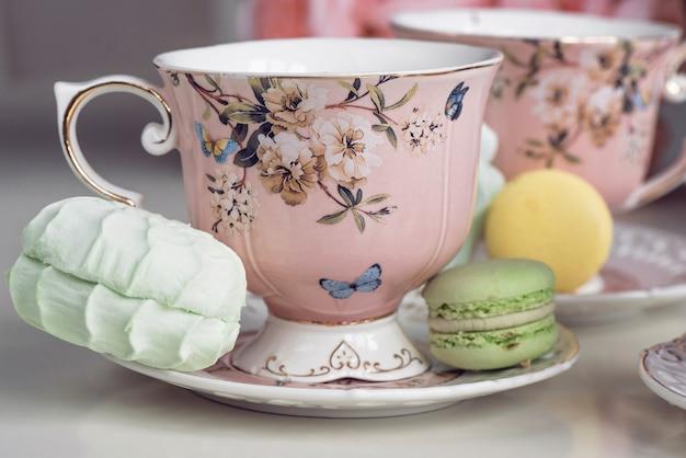 Tasses à thé rose avec ornement floral et bonbons macaron