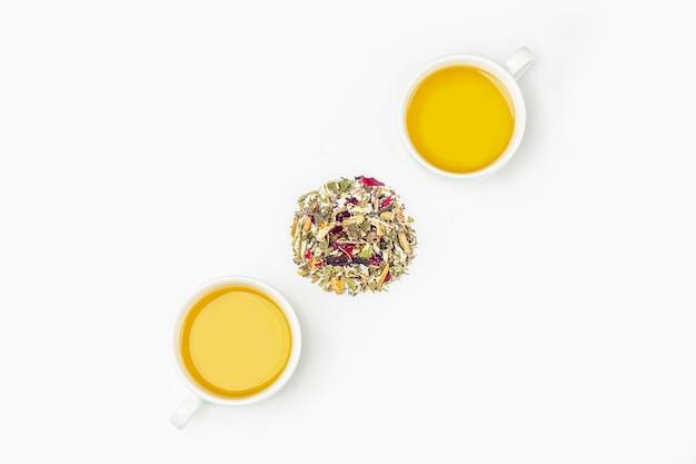 Tasses de thé vert avec cercle de feuilles de thé sec sur blanc