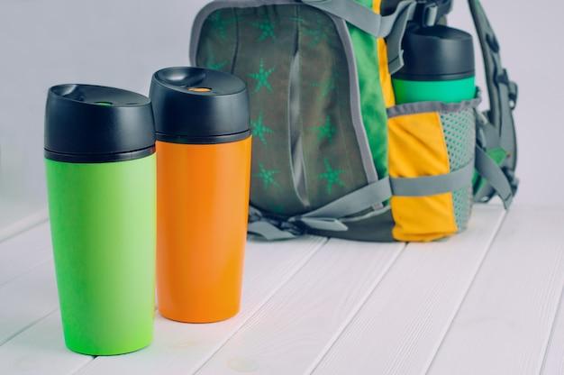 Tasses thermos devant le sac à dos