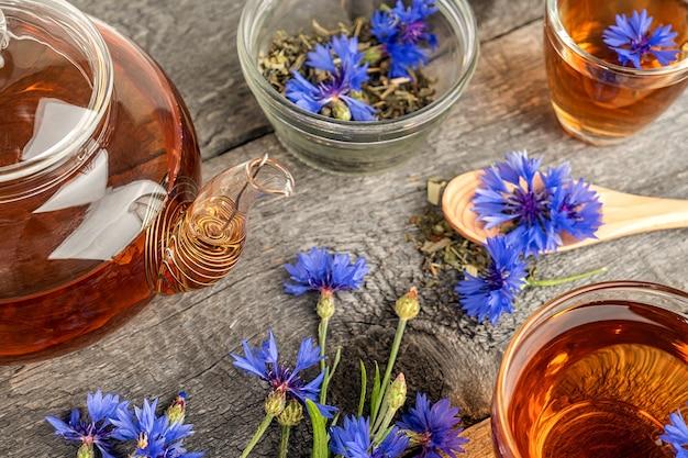 Tasses de tisane, théière transparente et bleuets fleurs bleues sur la surface du bois