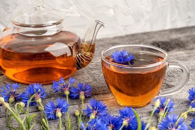 Tasses de tisane, théière transparente et fleurs de bleuets bleus
