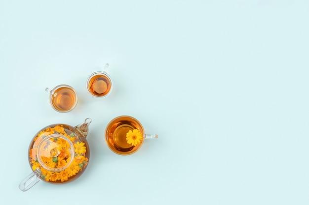 Tasses de tisane, théière transparente avec fleurs de calendula sur fond bleu. concept de boisson apaisante. espace de copie mise à plat vue de dessus.