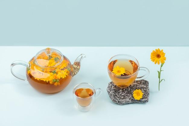 Tasses de tisane, théière transparente avec fleurs de calendula et pierres sur fond bleu. concept de boisson apaisante.