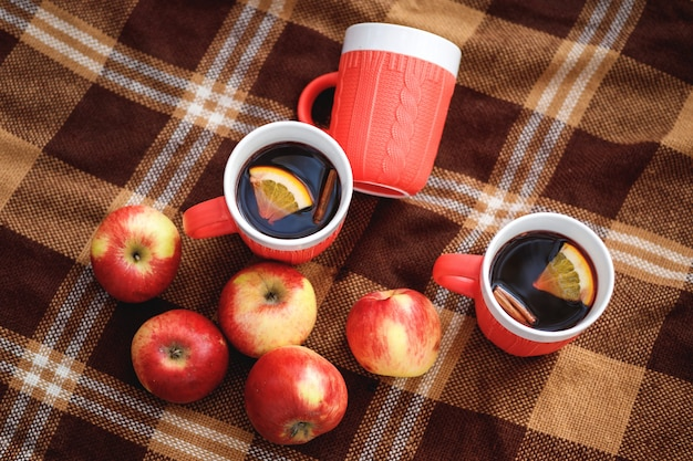 Tasses de vin chaud et pommes rouges sur une couverture