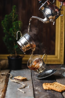 Tasses volantes en versant le thé chaud de la théière. lévitation.