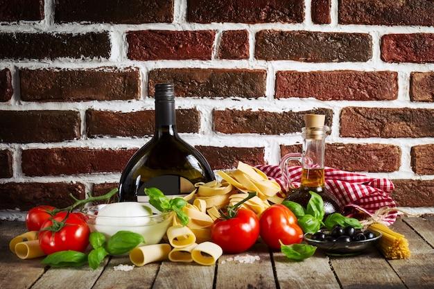 Tasty colorful fresh italian food concept avec divers pâtes spaghetti, mozzarella au fromage, basilic frais, tomates, huile d'olive, épices. concept de cuisine. lieu pour le texte.