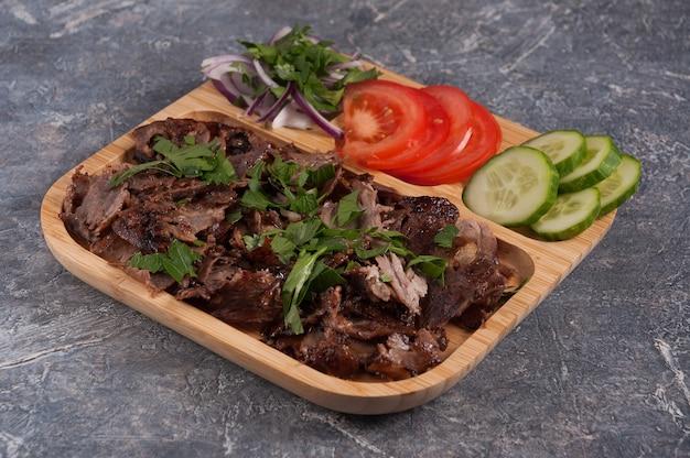 Tasty doner turc avec des concombres de veau, tomates et oignons sur une plaque en bois