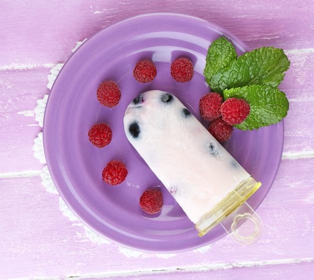 Tasty ice cream pop avec des baies fraîches sur plaque, sur bois de couleur