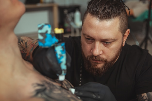Tatoueur barbu faisant des tatouages sur le corps de son client