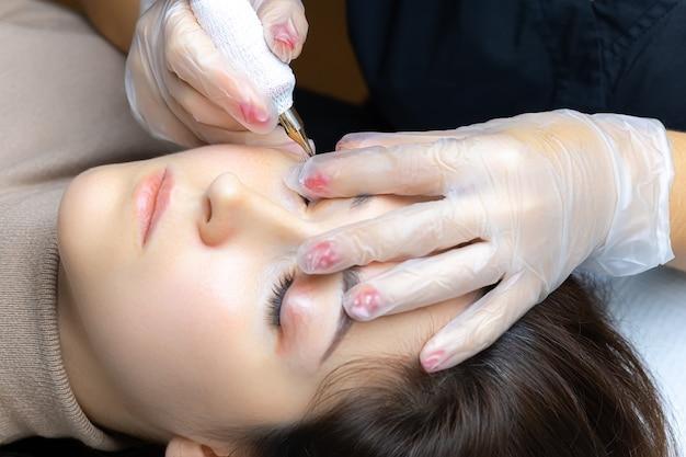 Le tatoueur étire les paupières du modèle et réalise un maquillage permanent des cils