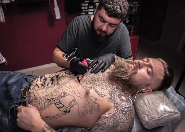 Le tatoueur fait du tatouage sur la peau de son client dans un studio de tatouage. / le tatoueur se concentre sur son travail en salon.