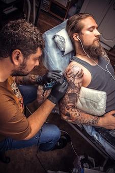 Le tatoueur fait des photos de tatouage dans un salon de tatouage.