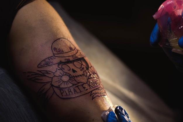 Le tatoueur fait un tatouage sur la main d'un homme. homme créant une image sur place avec elle dans le salon