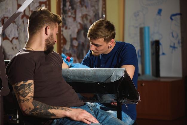 Le tatoueur fait un tatouage.