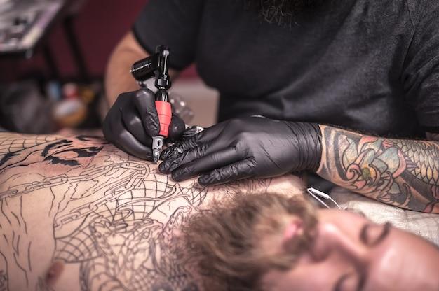 Le tatoueur fait des tatouages sur la peau de son client dans un studio de tatouage. / le spécialiste du tatouage fait des photos de tatouage dans le salon.