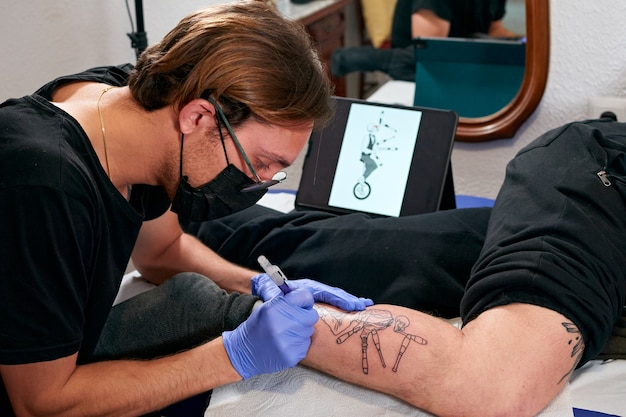 Le tatoueur en gants bleus et masque noir faisant un tatouage sur la jambe d'un homme dans un studio