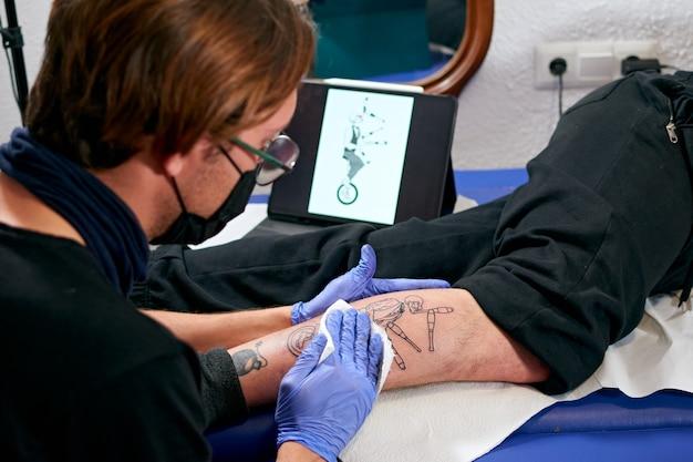 Un tatoueur en gants bleus regardant une tablette et faisant un tatouage sur la jambe d'un homme dans un studio