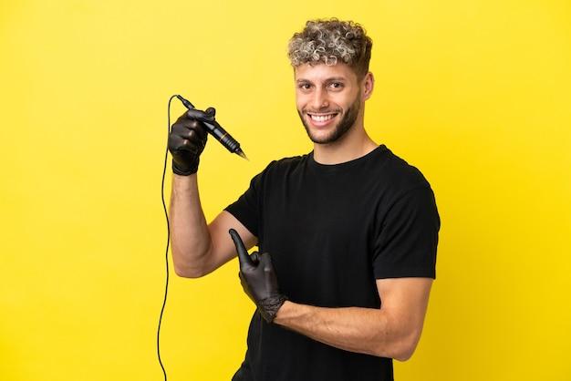 Tatoueur homme caucasien isolé sur fond jaune pointant vers l'arrière