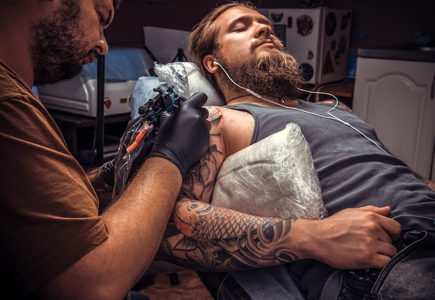 Tatoueur montrant le processus de fabrication d'un tatouage en studio de tatouage.