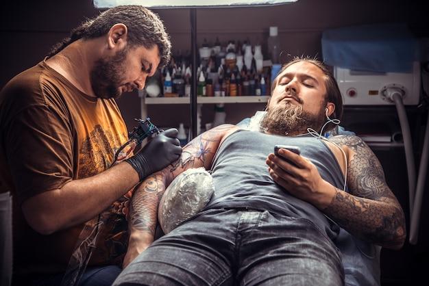 Tatoueur montrant le processus de fabrication d'un tatouage en studio