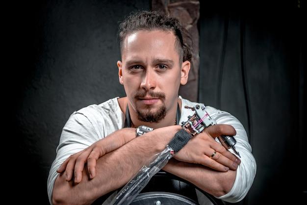 Tatoueur posant dans un salon / tatoueur professionnel pose dans un atelier.