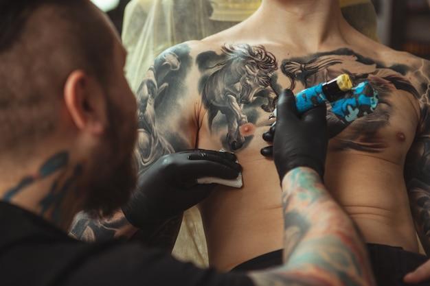 Tatoueur professionnel faisant un nouveau tatouage pour son client