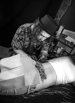 Tatoueur professionnel faisant une photo de tatouage dans son salon