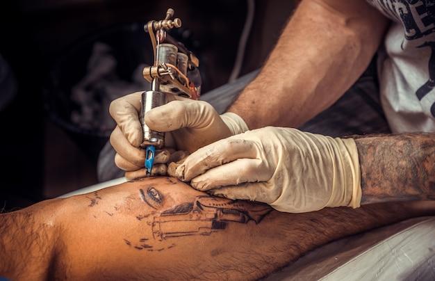 Un tatoueur professionnel fait des photos de tatouage dans un studio de tatouage