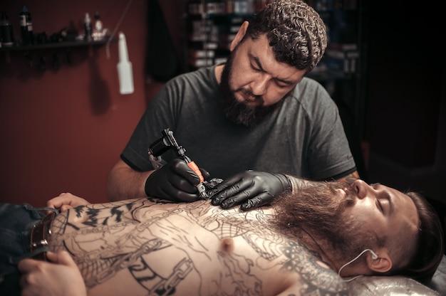 Un tatoueur professionnel fait un tatouage au salon.