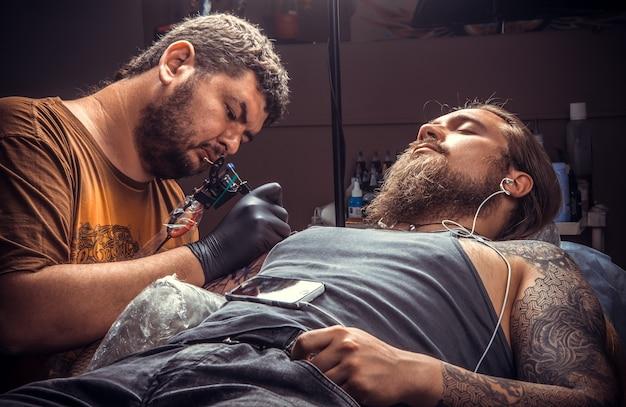 Un tatoueur professionnel fait un tatouage cool dans un studio de tatouage.