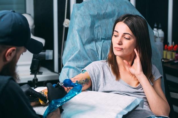 Un tatoueur professionnel fait un tatouage sur la main d'une jeune fille.