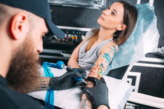 Tatoueur professionnel fait un tatouage sur la main de la jeune fille.