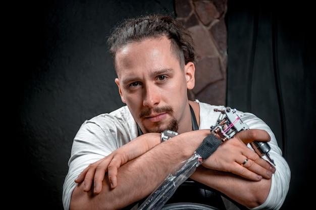 Le tatoueur professionnel pose pour la caméra dans le studio de tatouage.